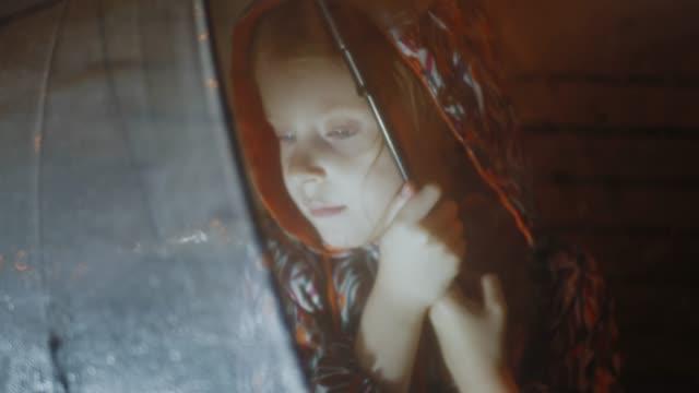 Little girl sits under wet transparent umbrella on bench in dark selective focus video