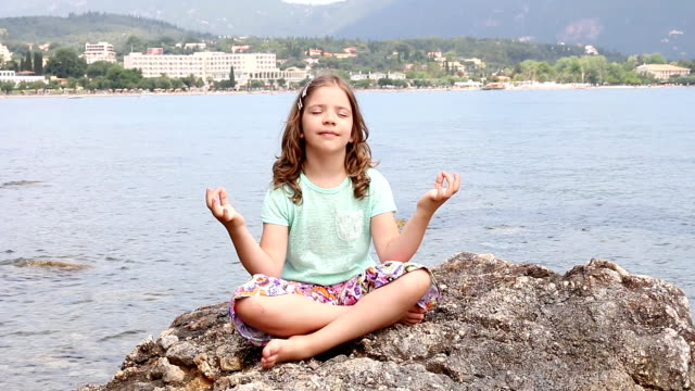 little girl sitting on a rock by the sea and meditates video