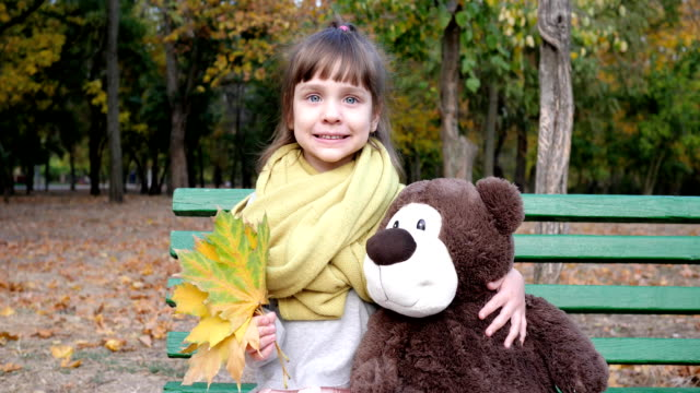 vídeos de stock e filmes b-roll de little girl sitting on bench with teddy bear and leaves in hands posing on background autumn park - teddy bear