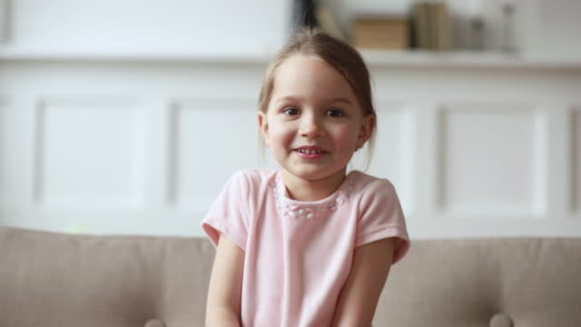 Little girl sitting on couch wave hand looking at camera