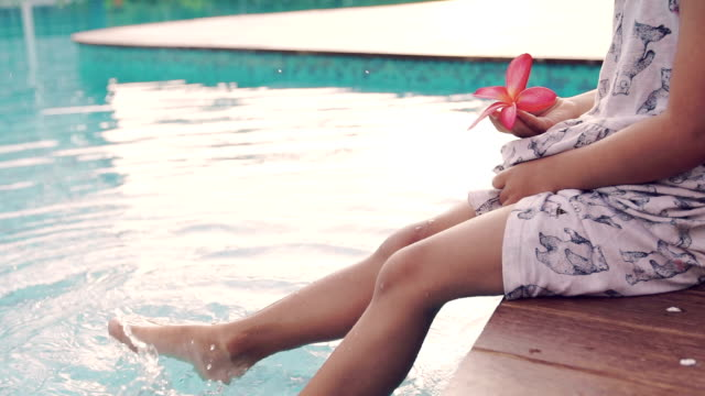 A little girl sitting on edge of pool with feet in water, video