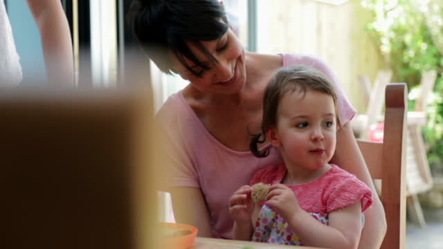 Little Girl Sitting on Her Mothers Lap Trying New Foods