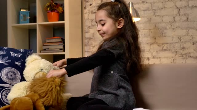 a little girl sitting on the couch and playing with a teddy bear and a lion, soft toys, home comfort in the background 50 fps - abbigliamento modesto video stock e b–roll