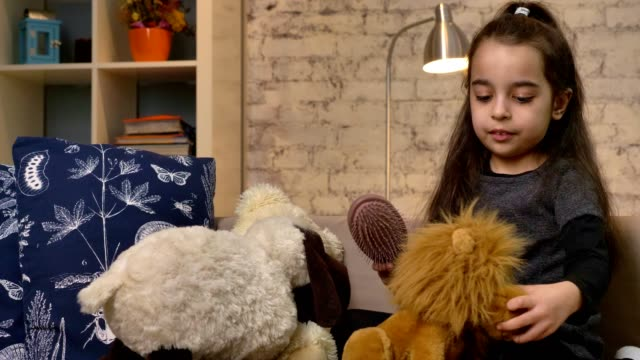 a little girl sitting on the couch and playing with a teddy bear and a lion, combs the fur of a toy lion, home comfort in the background 50 fps - abbigliamento modesto video stock e b–roll