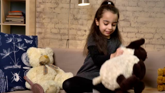 a little girl sitting on the couch and playing with a teddy sheep, soft toys, home comfort in the background 50 fps - abbigliamento modesto video stock e b–roll