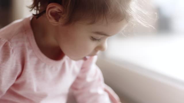 bambina seduta sul pavimento e disegno in salotto - matita colorata video stock e b–roll