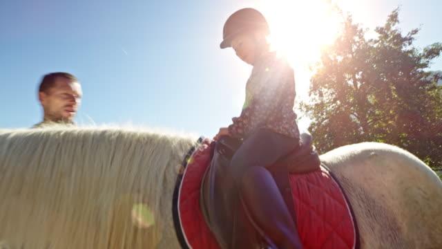 日差しの中で馬に乗っていた少女 - 動物に乗る点の映像素材/bロール