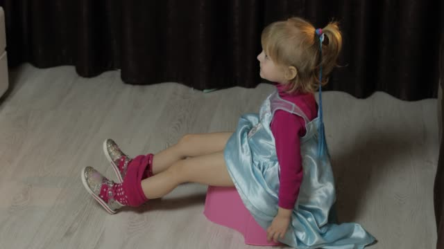 Little girl sitting on the potty and watching TV Little girl sitting on the potty and watching TV. blonde cute child in blue dress. Inside household fixture stock videos & royalty-free footage