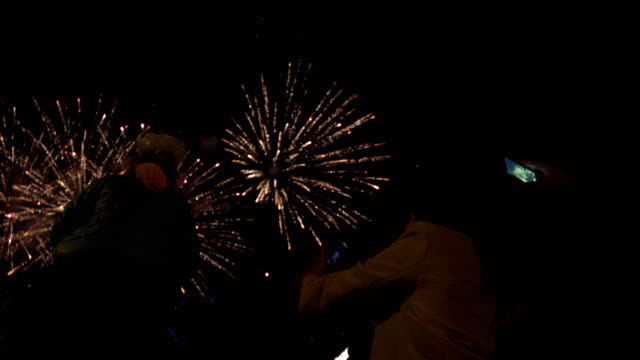 Little girl sitting on your dad's shoulders and watching fireworks. Concept of family relationships and Father's day. Viewers take pictures on smartphone. Firework - concept of finale of any holiday: Chinese new year, New year, Christmas, wedding video