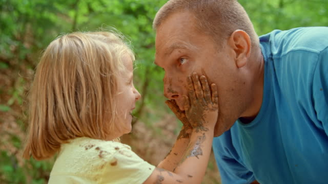 SLO MO Little girl smearing mud over her dad's face and laughing