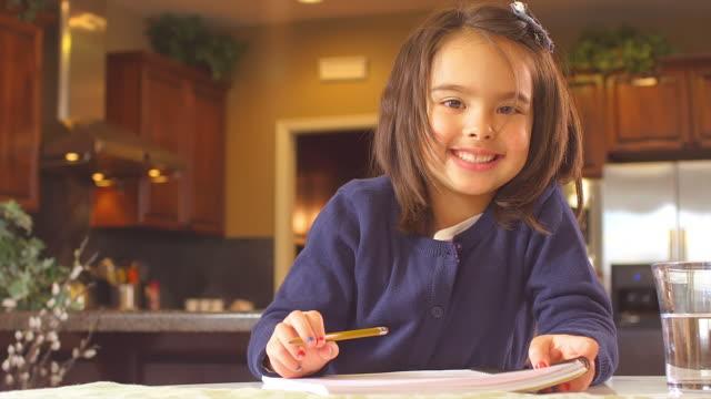 little girl smiles for the camera - çalışma kitabı stok videoları ve detay görüntü çekimi