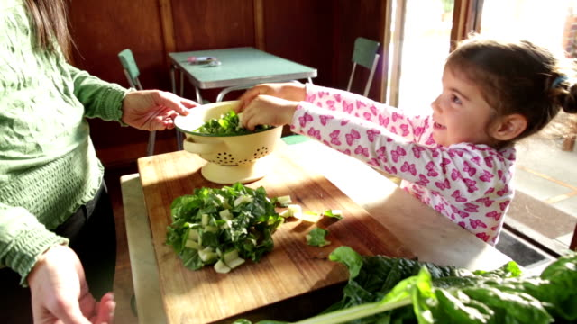 Little Girl Smiles helping her Mom in Kitchen video