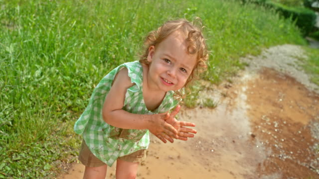 SLO MO Little girl smiling while dirtying her hands with mud and standing in the puddle with a stained top