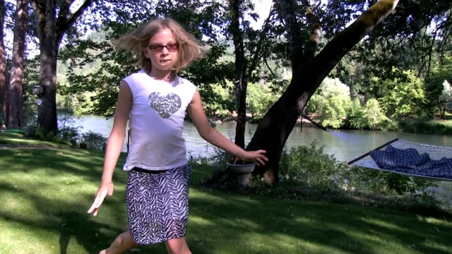 Little girl spins on grass and river slow motion 75% video
