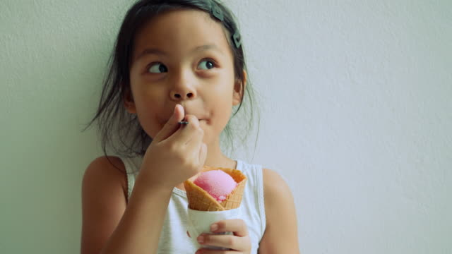 vídeos de stock e filmes b-roll de little girl standing eating ice cream and showing very happy face - ice cream