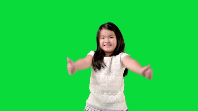 little girl standing in the studio while smiling at the camera and showing thumbs up video