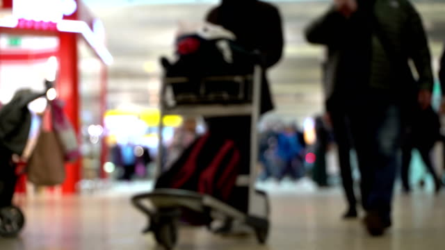 Little girl standing next to suitcase and looks on passing passenger and trolley at airport in blur. Family waiting at international airport terminal. Crowd of people at airport. Mother and daughter meet aircraft video