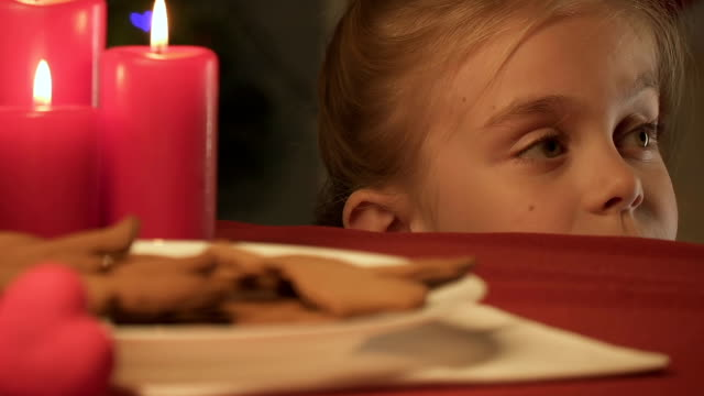 vídeos de stock e filmes b-roll de little girl stealing gingerbread cookie, magic christmas time in childhood - christmas cookies