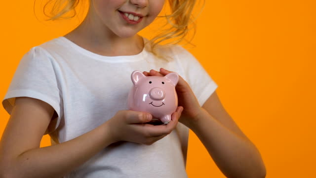 Little girl stroking piggy bank, personal savings and budget, planning future