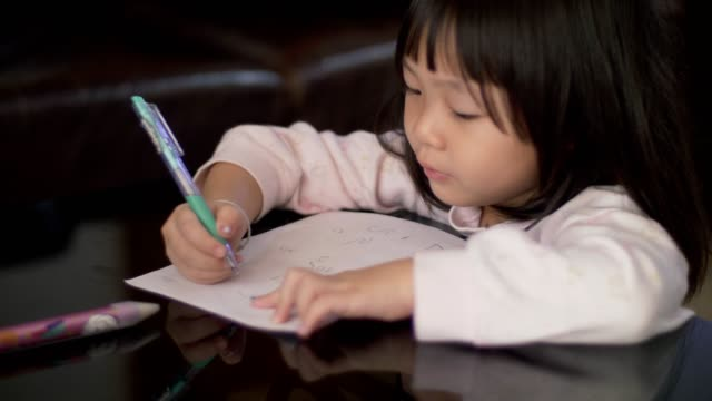 Little girl(4-5 years) study and learning writing on paper Handheld shot of asian little girl sitting in the living room study and learning writing on paper at home textbook stock videos & royalty-free footage