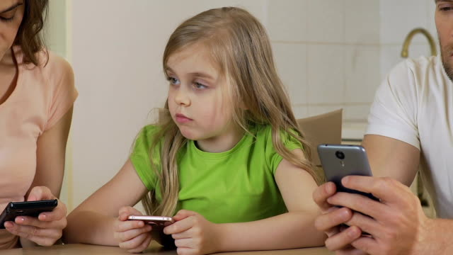 Little girl suffering from lack of parental warmth, mom and dad using phone Little girl suffering from lack of parental warmth, mom and dad using phone ignoring stock videos & royalty-free footage