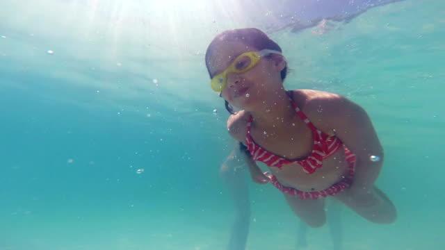 vídeos de stock e filmes b-roll de menina nada subaquática alcançar a mão do pai - brinquedos na piscina