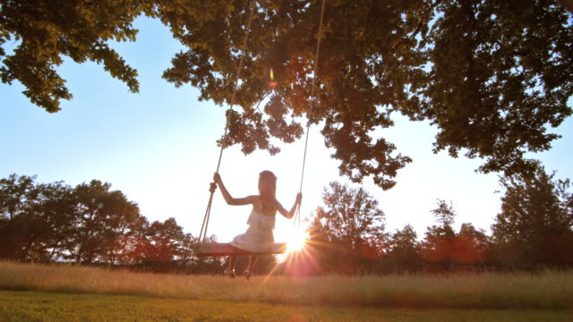 SLO MO Little girl swinging at sunset Slow motion medium locked down shot of a little girl in a white dress and braided hair swinging under a big tree at sunset. swinging stock videos & royalty-free footage