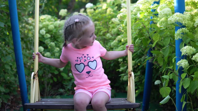 Little girl swinging on a swing and trying to swing harder