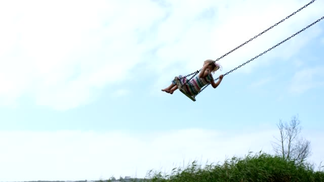 Little girl swinging on a wooden swing A little girl swings high on a wooden swing on a cloudy day. swinging stock videos & royalty-free footage