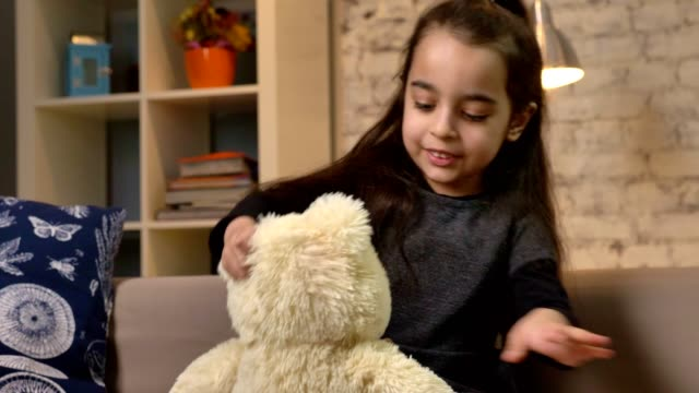 little girl takes a teddy bear on her hands, sitting on the couch, home comfort in the background 50 fps - abbigliamento modesto video stock e b–roll