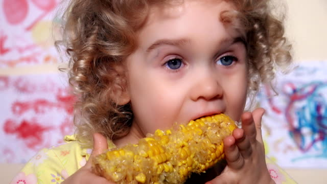 little girl taking a bite out of a corn on the cob video