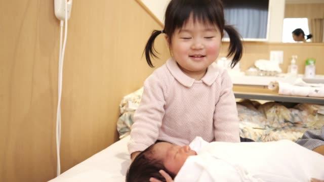 母親との新生の赤ちゃんの世話をする小さな女の子 - 母娘 笑顔 日本人点の映像素材/bロール