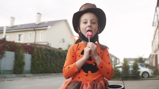 Little girl taking off protective face mask and eating lollipop on Halloween