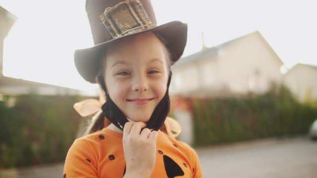 vídeos y material grabado en eventos de stock de niña quitándose la máscara protectora de la cara y sonriendo en halloween - halloween covid