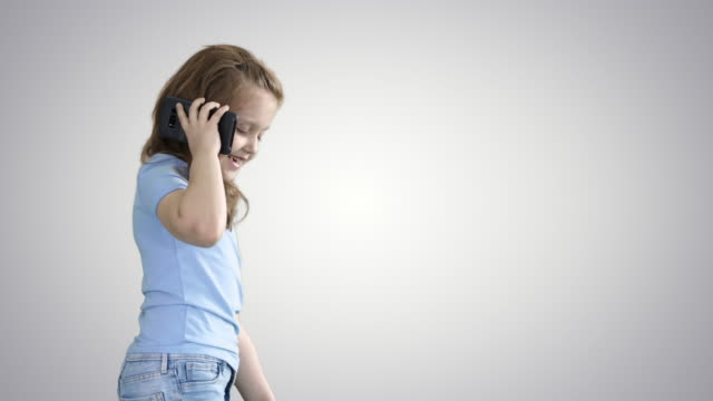 Little girl talk phone and walking on gradient background