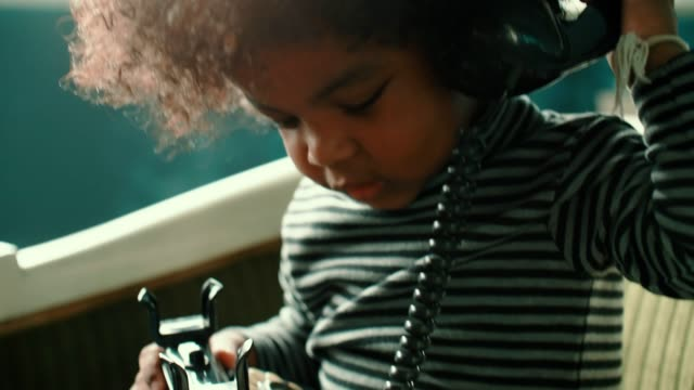 Little girl talking on telephone at home Handheld shot of african-american girl(2-3 years) sitting on vintage chair and using rotary phone, 4K Resolution landline phone stock videos & royalty-free footage
