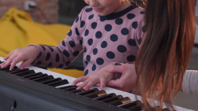 Little girl teaching to play synthesizer