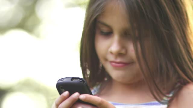 stockvideo's en b-roll-footage met little girl texting - infaden