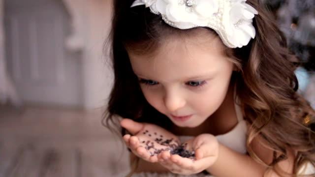 petite fille trois ans soufflant sur des paillettes d'argent - Vidéo