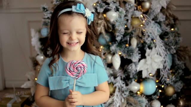 petite fille trois ans dans une robe bleue lèche - Vidéo