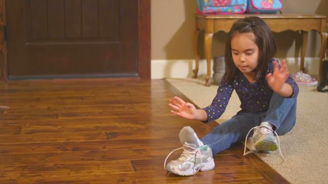 LIttle girl ties her shoe. video