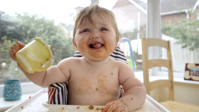 vídeos de stock, filmes e b-roll de menina bebê comendo confuso na cadeira alta - desarrumado