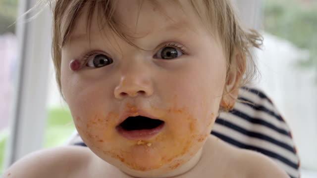 vídeos y material grabado en eventos de stock de niña niño pequeño desordenado comer en una silla alta - lunares