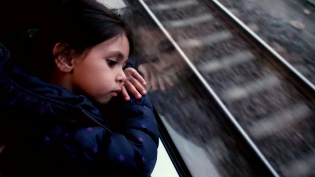 Little girl traveling in train looking outside the window.