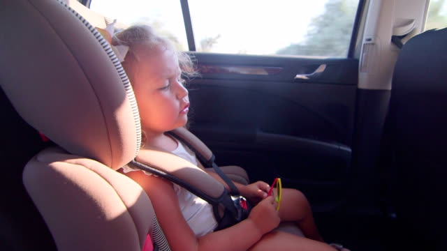 Little girl traveling with family by car singing road trip song video