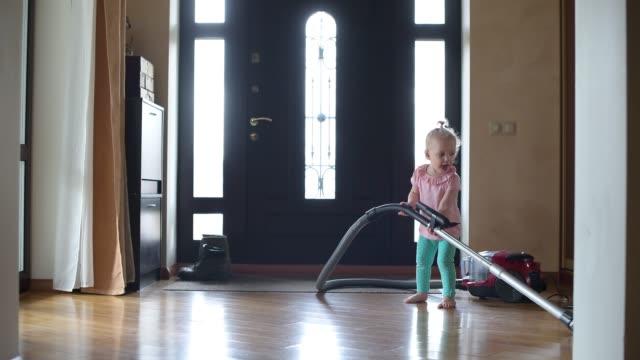 küçük kız evde koridorda vakum çalışıyor. bir komik video - ev temizleme stok videoları ve detay görüntü çekimi