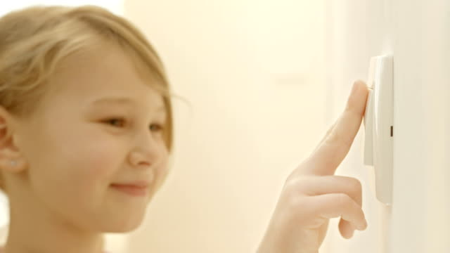Little Girl Turning On The Lights HD1080p: Little girl approaching a camera where she turning on the lights by pressing a light switch. start button stock videos & royalty-free footage