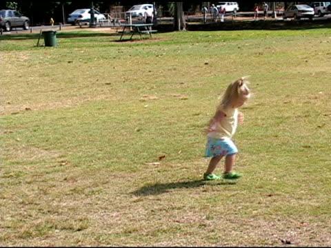 little girl turns circles at the park - endast flickor bildbanksvideor och videomaterial från bakom kulisserna