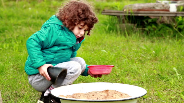 Little girl using a plastic cone to scoop sand into the red bowl video