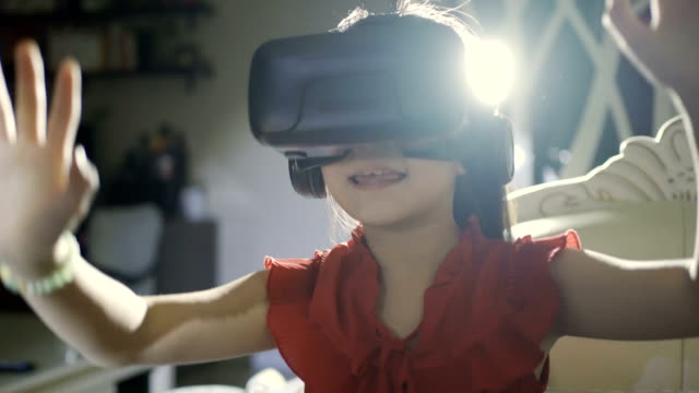 Little girl using a virtual reality glasses at home